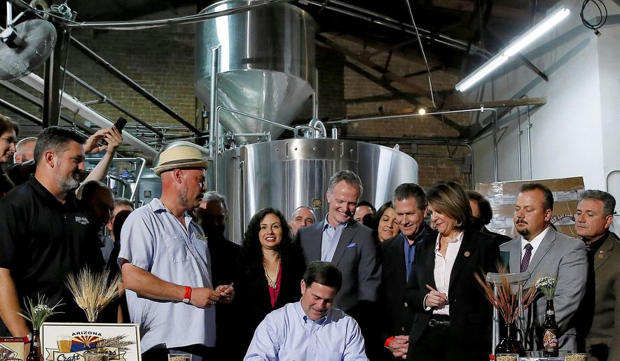 FILE - In this March 31, 2015 file photo, Arizona Gov. Doug Ducey, center, signs Senate Bill 1030, at Four Peaks Brewery in Tempe, Ariz. The growing Tempe, Arizona-based craft brewer on Friday, Dec. 18, 2015, became the latest microbrewery bought by a beer giant Anheuser-Busch InBev, as major industry players move into the niche market that has captured more than 10 percent of beer sales in recent years. (AP Photo/Matt York, File)