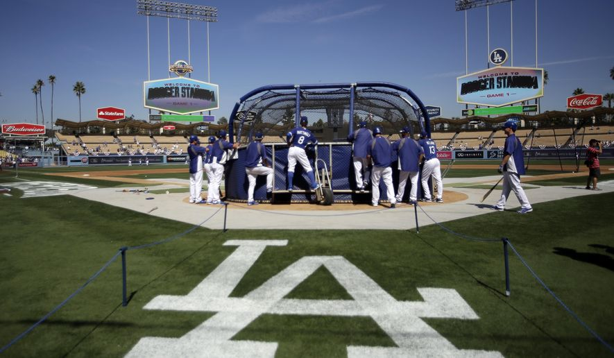 FILE - In this Oct. 3, 2014, file photo, Los Angeles Dodgers players watch batting practice before Game 1 of baseball's NL Division Series against the St. Louis Cardinals in Los Angeles. The  Dodgers have been hit with a record luxury tax of nearly $43.6 million for a payroll that fell just shy of $300 million. (AP Photo/Alex Gallardo, File)