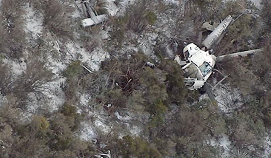 FILE - This undated still image taken from video provided by ABC-15, shows a medical helicopter after it crashed in rugged terrain east of Phoenix, killing two crew members and seriously injuring a third. An Air Force officer who helped rescue the sole survivor of the crash says the wreckage was perched precariously on a rocky Arizona mountainside. And the seriously injured survivor was right below the wreckage, where he would have been crushed if the wreckage rolled downhill during the nighttime rescue. (ABC-15.com via AP, File) MANDATORY CREDIT. TV OUT