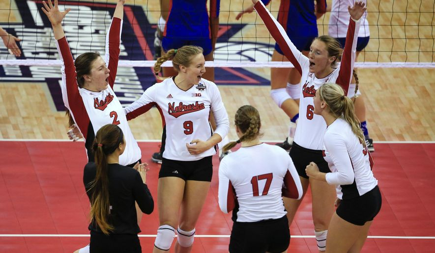 Nebraska players celebrate a point against Kansas during an NCAA women's volleyball tournament semifinal in Omaha, Neb., Thursday, Dec. 17, 2015. (AP Photo/Nati Harnik)
