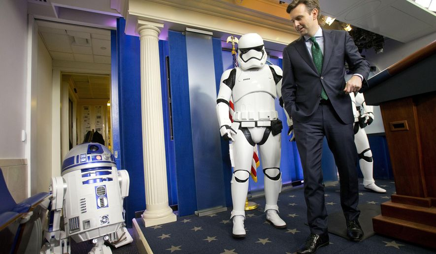 White House Press secretary Josh Earnest is joined by Star Wars Storm Troopers and R2D2 in the Brady Press Briefing Room of the White House, Friday, Dec. 18, 2015. The movie characters will greet children of Gold Star families who are attending a special screening of Star Wars: The Force Awakens later today at the White House Family Theater. (AP Photo/Pablo Martinez Monsivais)