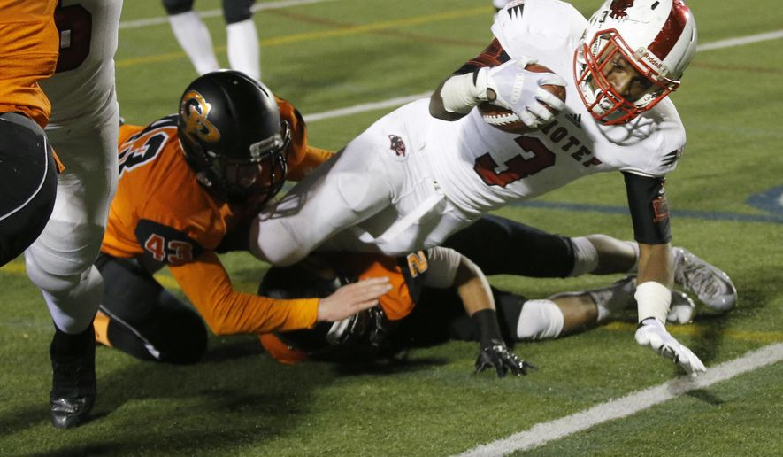 Imhotep Charter's Isheem Young, right,  dives through the grasp of Cathedral Prep's John Oehling, left, for a successful two-point conversion during the first quarter of the PIAA Class AAA state championship high school football game, Friday, Dec. 19, 2015, in Hershey, Pa. (Charles Fox/The Philadelphia Inquirer via AP)  PHIX OUT; TV OUT; MAGS OUT; NEWARK OUT; MANDATORY CREDIT