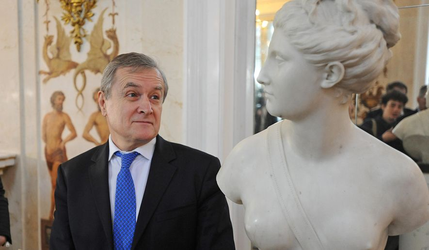Poland's Culture Minister Piotr  Glinski looks the marble bust of the antique goddess Diana during a ceremony of return at the Lazienki Palace in Warsaw, Poland, Friday, Dec. 18, 2015. The 18th-century marble bust of the goddess Diana looted by the Nazis in 1940 has returned to Warsaw from Vienna, where it recently surfaced at an auction house. The return of the sculpture, by French master Jean-Antoine Houdon and valued at some 250,000 euro (US dlrs 271,000), is the latest development in Poland's yearslong effort to retrieve tens of thousands of works of art looted from museums and private collections in the nation's tumultuous history, most recently during World War II.  (AP Photo/Alik Keplicz)