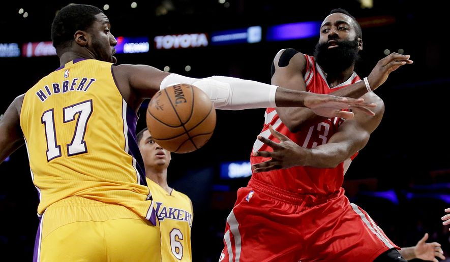 Houston Rockets guard James Harden, right, passes around Los Angeles Lakers center Roy Hibbert during the first half of an NBA basketball game in Los Angeles, Thursday, Dec. 17, 2015. (AP Photo/Chris Carlson)