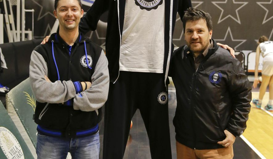 In this Saturday, Dec. 5, 2015, photo, Robert Bobroczkyi, center, poses for a photo with Stellazzurra Basketball Academy general manager Giacomo Rossi, left, and club president Fabio de Mita during an interview in Rome. Standing 7-foot-6 (2.29 meters) at the age of 15, Robert Bobroczkyi is already taller than New York Knicks sensation Kristaps Porzingis, or any other current NBA player. (AP Photo/Andrew Medichini)