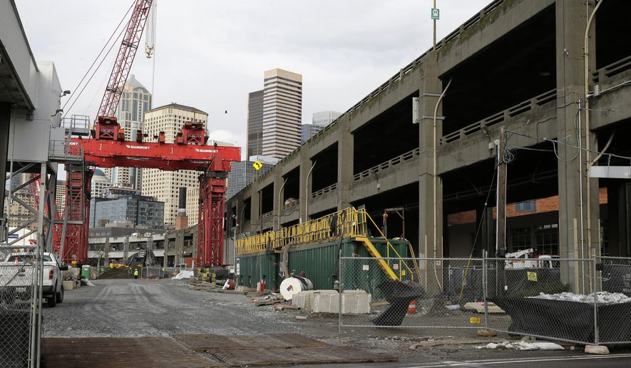 """A crane is shown Friday, Dec. 18, 2015, at the site in Seattle, where an access pit had been dug to repair """"Bertha,"""" the massive tunnel boring machine digging a replacement for the Alaskan Way Viaduct elevated roadway, after it hit an underground pipe more than two years ago. Officials have said that the machine could resume tunneling as early as next week.  (AP Photo/Ted S. Warren)"""