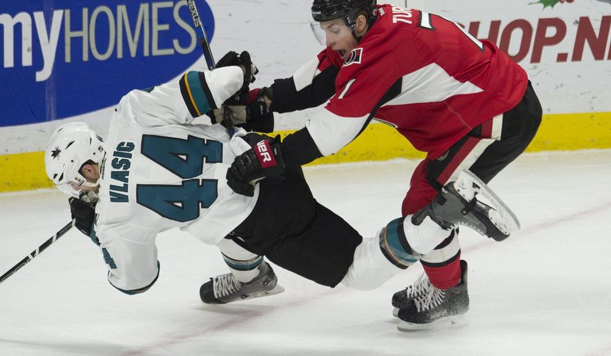 Ottawa Senators center Kyle Turris pushes San Jose Sharks defenseman Marc-Edouard Vlasic off the puck during first-period NHL hockey game action Friday, Dec. 18, 2015, in Ottawa, Ontario. (Adrian Wyld/The Canadian Press via AP) MANDATORY CREDIT