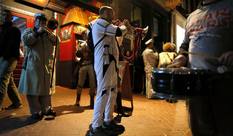 "A member of the Intergalactic Krewe of Chewbacchus plays an instrument, Thursday, Dec. 17, 2015, in New Orleans. The group, a Mardi Gras parade club, is celebrating the premiere of the latest ""Star Wars"" movie with costumes, a brass band and a parade through the French Quarter. (AP Photo/Jonathan Bachman)"