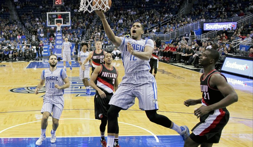Orlando Magic's Tobias Harris (12) makes a shot as he gets between Portland Trail Blazers' Noah Vonleh (21) and C.J. McCollum (3) during the first half of an NBA basketball game, Friday, Dec. 18, 2015, in Orlando, Fla. (AP Photo/John Raoux)