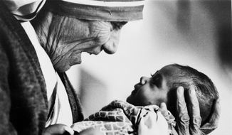 In this 1978 file photo, Mother Teresa, head of the Missionaries of Charity order, cradles an armless baby girl at her order's orphanage in what was then known as Calcutta, India. Pope Francis has signed off on the miracle needed to make Mother Teresa a saint, giving the nun who cared for the poorest of the poor one of the Catholic Church's highest honors just two decades after her death. (AP Photo/Eddie Adams, File)