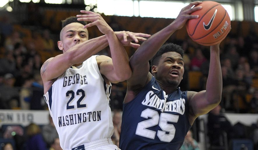 George Washington guard Joe McDonald (22) battles for the ball against St. Peter's guard Cameron Jones (25) during the second half of an NCAA college basketball game, Saturday, Dec. 19, 2015, in Washington. George Washington won 87-74. (AP Photo/Nick Wass)