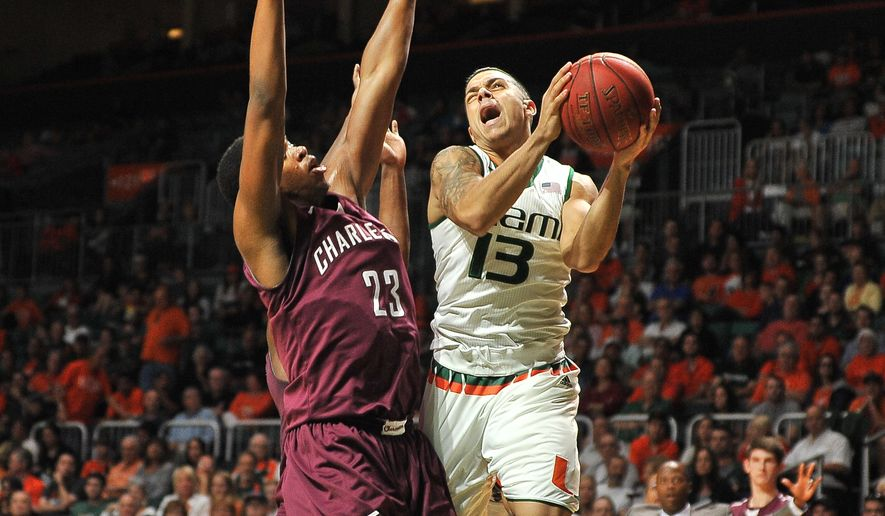 Miami's Angel Rodriguez attempts a lay up as Nick Harris of  Charleston blocks during an NCAA college basketball game in Coral Gables, Fla., Saturday, Dec. 19, 2015. (AP Photo/Gaston De Cardenas)