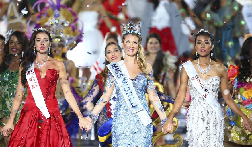 Miss World Mireia Lalaguna Royo from Spain, center, Sofia Nikitchuk from Russia, left, the runner-up, and Maria Harfanti from Indonesia, right, the second runner-up celebrate at the end of the 2015 Miss World Grand Final in Sanya in south China's Hainan province Saturday Dec. 19, 2015. Spain's Mireia Lalaguna Royo was named the winner of the Miss World 2015 competition Saturday night in the southern Chinese island resort of Sanya, an event dogged by controversy over China's refusal to allow Canada's entrant to attend. (Chinatopix Via AP) CHINA OUT