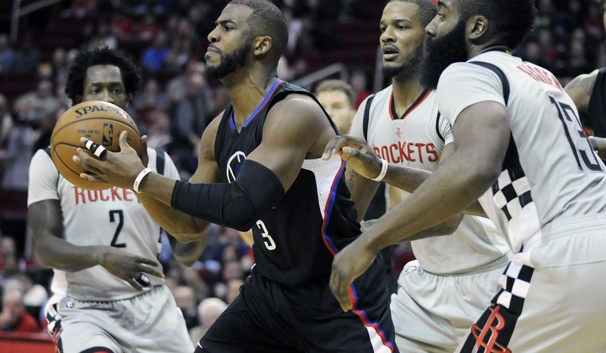 Los Angeles Clippers' Chris Paul (3) is surrounded by Houston Rockets Patrick Beverley (2), Trevor Ariza and James Harden (13) as he passes off the ball in the first half of an NBA basketball game Saturday, Dec. 19, 2015, in Houston. (AP Photo/Pat Sullivan)