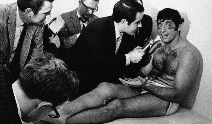 FILE - In this Jan. 13, 1969, file photo, New York Jets quarterback Joe Namath talks with reporters as he rests on a training table in the teams dressing room the morning after the Jets defeated the Baltimore Colts 16-7 in Super Bowl III in Miami, Fla. (AP Photo/File)