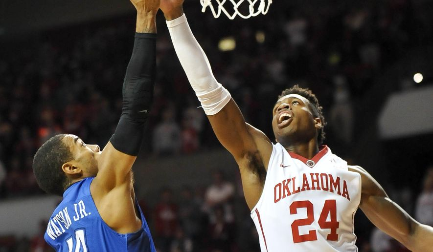 Oklahoma guard Buddy Hield (24) tries to block a shot by Creighton guard Maurice Watson Jr. (10) during the first half of an NCAA basketball game in Norman, Okla., Saturday, Dec. 19, 2015. (AP Photo/Kyle Phillips)