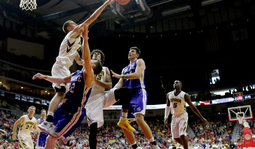 Iowa forward Nicholas Baer blocks the shot of Drake guard Reed Timmer during the first half of an NCAA college basketball game, Saturday, Dec. 19, 2015, in Des Moines, Iowa. (AP Photo/Justin Hayworth)