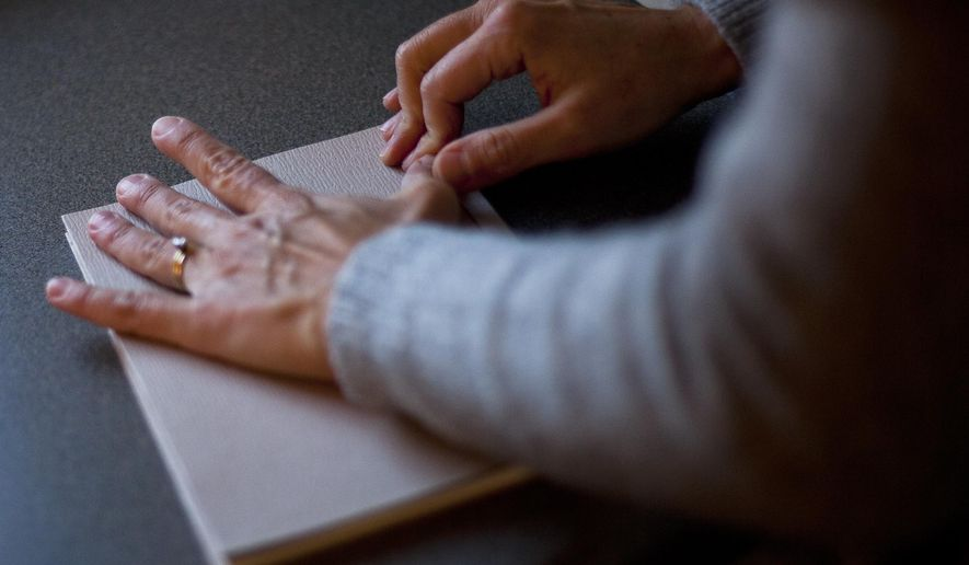In this photo taken Friday, Dec. 4, 2015, Jill Krase uses a bone folder to flatten together the cover of a book she is binding at her home studio in Winona, Minn. Krase has been bookbinding in Winona for more than 10 years. She operates Ovenbird Bindery out of her home studio, where she makes books and boxes, binds limited editions, repairs books, and teaches others her trade. (Chuck Miller/The Winona Daily News via AP) MANDATORY CREDIT