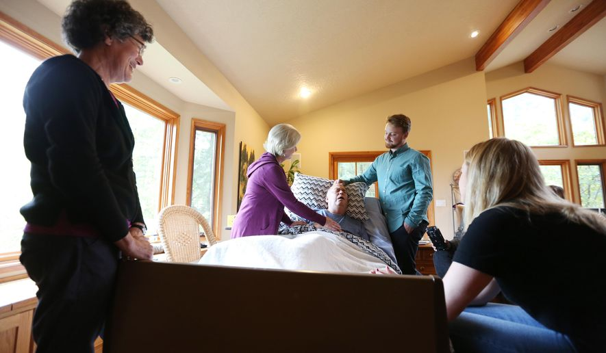 ADVANCE FOR WEEKEND EDITIONS, DEC. 19-20 - In this photo taken Oct. 8, 2015, Dr. Peter Rasmussen lies in bed surrounded by family and friends, including Joan Stembridge, left; his wife, Cindy; stepson, Keith Brandtjen and stepdaughter, Gretchen Higgins, at his home in Salem, Ore., home. Rasmussen, a retired oncologist and advocate for physician aid-in-dying, died Nov. 3 using Oregon's Death with Dignity law. (Danielle Peterson/Statesman-Journal via AP) MANDATORY CREDIT