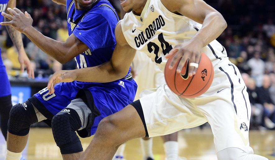 George King, of Colorado, drives on Brian Darden, of Hampton, during the first half of an NCAA college basketball game Saturday, Dec. 19, 2015, in Boulder, Colo. (Cliff Grassmick/Daily Camera via AP)
