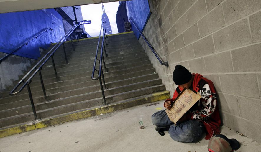 FILE - In this Oct. 9, 2015 file photo, a homeless man holds a sign asking for money while sitting at the entrance to a subway station in New York. New York City plans to deploy hundreds of outreach workers who will canvass much of Manhattan every day with a deceptively simple goal: talk to as many homeless people as possible, as often as possible. Through frequent contact, the city hopes to persuade the chronic homeless, even those living on the street for years, to go to shelters. (AP Photo/Mark Lennihan, File)