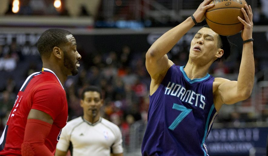 Charlotte Hornets guard Jeremy Lin (7) is temporarily off balance before recovering during play against Washington Wizards guard John Wall in the first half of an NBA basketball game in Washington, Saturday, Dec. 19, 2015. (AP Photo/Jacquelyn Martin)