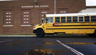 In this Thursday, Dec. 17, 2015 photo, a school bus waits outside of Riverheads High School in Staunton, Va., after Augusta County Schools were placed on lockdown in the afternoon. The closure was prompted by security concerns due to thousands of angry emails and social media postings after a teacher's lesson on Islam at Riverheads High School the previous week. (Griffin Moores/The Staunton News Leader via AP) **FILE**
