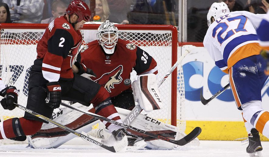 Arizona Coyotes' Louis Domingue (35) gets ready to make a save on a shot by New York Islanders' Anders Lee (27) as Coyotes' Nicklas Grossmann (2), of Sweden, slides over in an attempt to deflect the puck during the second period of an NHL hockey game Saturday, Dec. 19, 2015, in Glendale, Ariz. (AP Photo/Ross D. Franklin)