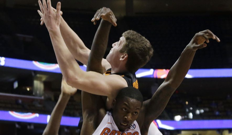 Oklahoma State's Mitchell Solomon goes for a rebound against Florida 's Dorian Finney-Smith (10) in the first half of the NCAA college Orange Bowl Basketball Classic, Saturday, Dec. 19, 2015, in Sunrise, Fla. (AP Photo/Lynne Sladky)