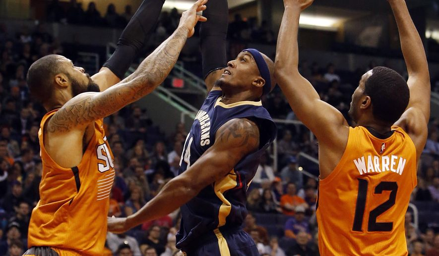 New Orleans Pelicans forward Dante Cunningham, middle, drives between Phoenix Suns' Markieff Morris, left, and T.J. Warren during the second quarter of an NBA basketball game, Friday, Dec. 18, 2015, in Phoenix. (AP Photo/Rick Scuteri)