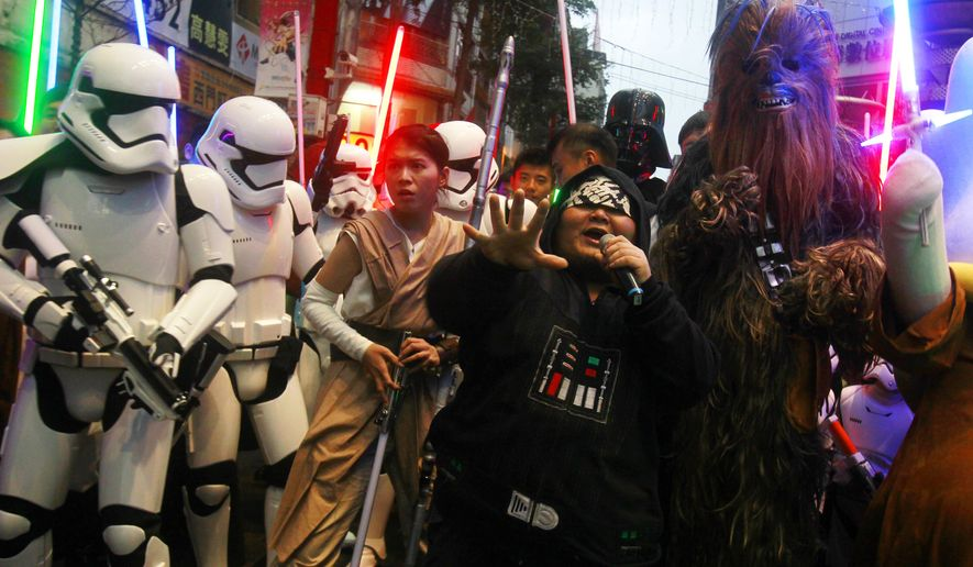 "Fans dressed as Star Wars characters parade outside a movie theater showing ""Star Wars: The Force Awakens"" Saturday, Dec. 19, 2015, in Taipei, Taiwan. (AP Photo/Chiang Ying-ying)"