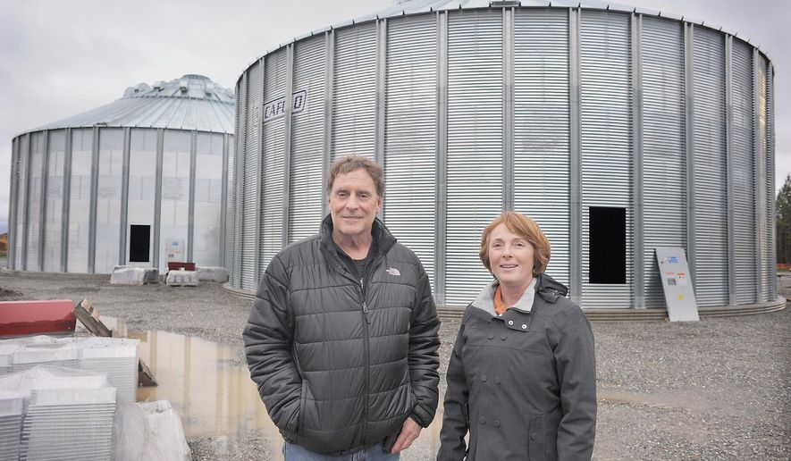ADVANCE FOR SUNDAY, DEC. 20 AND THEREAFTER - Skagit Valley Malting founder Wayne Carpenter and Skagit Port executive director Patsy Martin stand ouside two large silos under construction that are part of the malting company's expansion at the Port of Skagit County in Burlington, Wash., Thursday, Dec 10, 2015. Originally conceived in collaboration with the Port of Skagit to increase the value of local grain, Skagit Valley Malting is malting and germinating grains no one else can. (Scott Terrell/Skagit Valley Herald via AP)