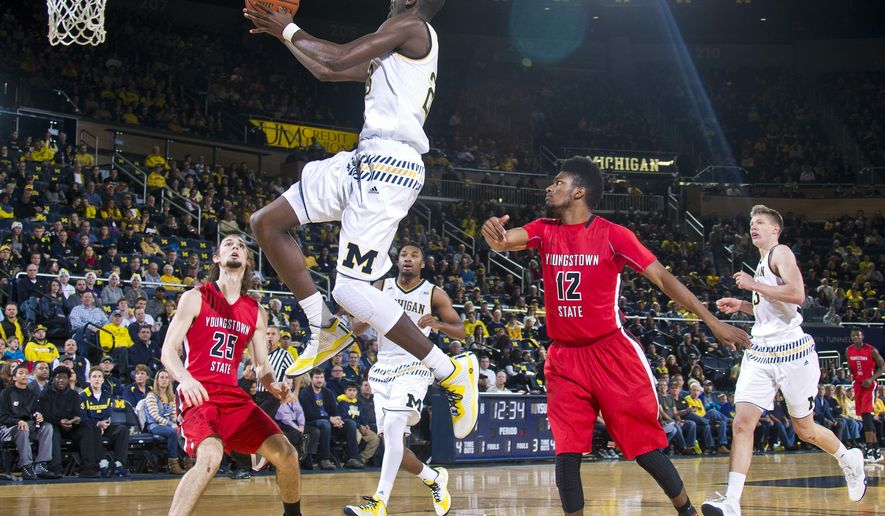 Michigan guard Caris LeVert, top, goes to the basket, defended by Youngstown State guard Jordan Andrews (25) and guard Cameron Morse (12) in the first half of an NCAA college basketball game in Ann Arbor, Mich., Saturday, Dec. 19, 2015. (AP Photo/Tony Ding)