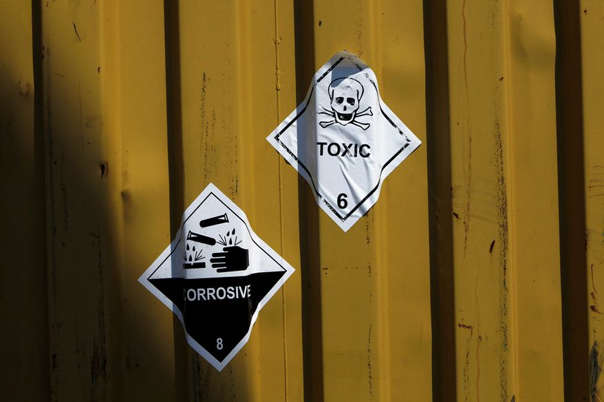 """Signs reading """"Toxic"""" and """"Corrosive"""" are stuck to containers carrying Syrian chemical weapons aboard the Danish cargo ship Ark Futura in Cyprus coastal waters as they are transported out of the strife-torn country on May 13, 2014. (Associated Press)"""