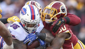 Buffalo Bills running back Mike Gillislee (35) is stopped by Washington Redskins strong safety Kyshoen Jarrett (30) during the second half of an NFL football game against in Landover, Md., Sunday, Dec. 20, 2015. (AP Photo/Andrew Harnik)