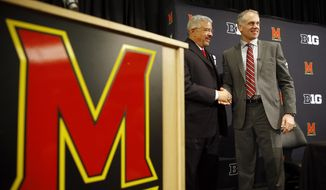 D.J. Durkin, right, poses for photographers alongside Maryland athletic director Kevin Anderson after being introduced as Maryland's new head football coach, Thursday, Dec. 3, 2015, in College Park, Md. Durkin comes from the University of Michigan, where he was the defensive coordinator and linebackers coach. (AP Photo/Patrick Semansky)