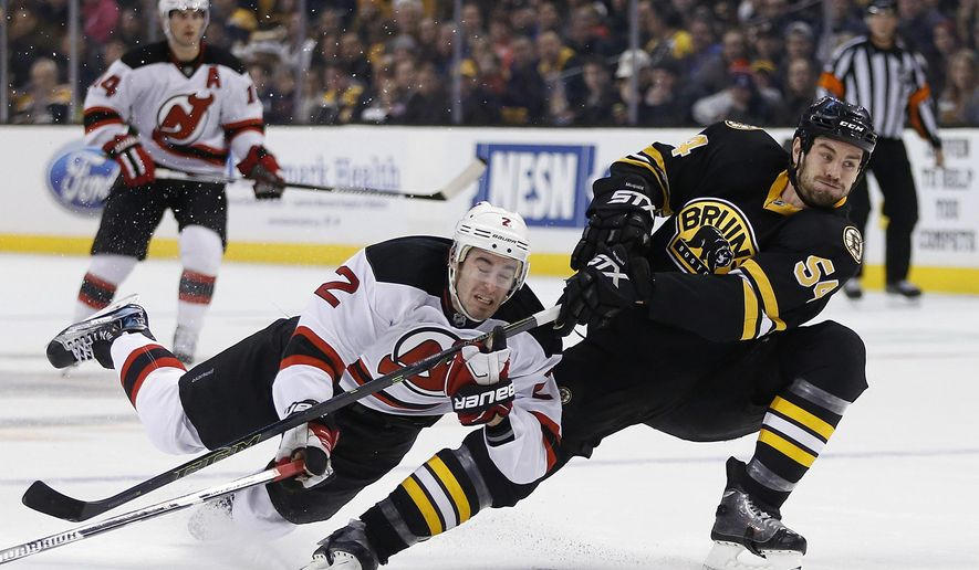 New Jersey Devils' John Moore (2) becomes entangled with Boston Bruins' Adam McQuaid (54) during the first period of an NHL hockey game in Boston, Sunday, Dec. 20, 2015. (AP Photo/Michael Dwyer)