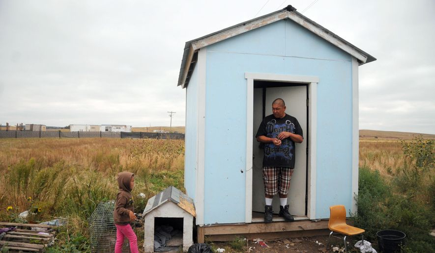 In this Wednesday, Sept. 30, 2015, photo, Raymond Eagle Hawk, right, stands in the doorway of his home that he shares with his daughter, Kimimila Eagle Hawk, left, and his girlfriend in Wounded Knee, S.D., on the Pine Ridge Indian Reservation. The housing shortage on South Dakota's Pine Ridge Indian Reservation is a longstanding problem for thousands of Oglala Sioux members, but the tribe is pushing the issue into the spotlight again after severe storms and flooding in May spurred a federal disaster declaration. (AP Photo/James Nord)