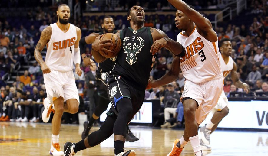 Milwaukee Bucks guard O.J. Mayo, left, drives on Phoenix Suns guard Brandon Knight in the second quarter during an NBA basketball game, Sunday, Dec. 20, 2015, in Phoenix. (AP Photo/Rick Scuteri)