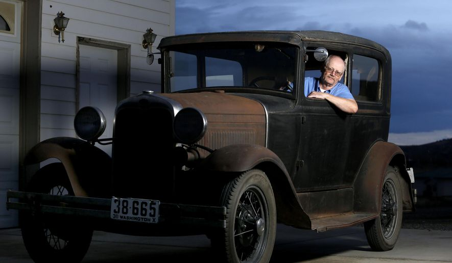 In this Dec. 8, 2015, photo, Tom Eldhardt poses for a photo in his 1930 Ford Model A Tudor at the shop where he works on cars outside his home in West Richland, Wash. Eldhardt is featured in the December issue of Hemmings Classic Car, a magazine aimed at car collectors. (Sarah Gordon/The Tri-City Herald via AP) LOCAL TELEVISION OUT; LOCAL RADIO OUT KONA