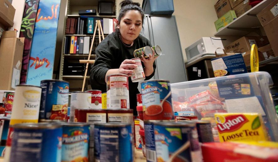 Samantha Arriozola sorts through donations for the Open Seat, an on-campus food pantry for poor University of Wisconsin-Madison students at the school in Madison, Wis., Sunday, Dec. 20, 2015. The group wants to make it easier for hungry college students by opening a food pantry on the campus. (M.P. King/Wisconsin State Journal via AP) MANDATORY CREDIT