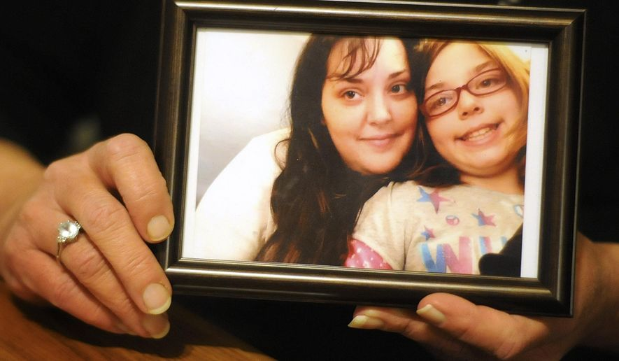 In this Nov. 27, 2015 photo, Cindy Kennedy holds a photo of her daughter, Lisa Ayres, and Lisa's daughter, Marisa McKune, at her home in Kankakee, Ill. Lisa died of a heroine overdose at the age of 32. (Mike Voss/The Daily Journal via AP) MANDATORY CREDIT
