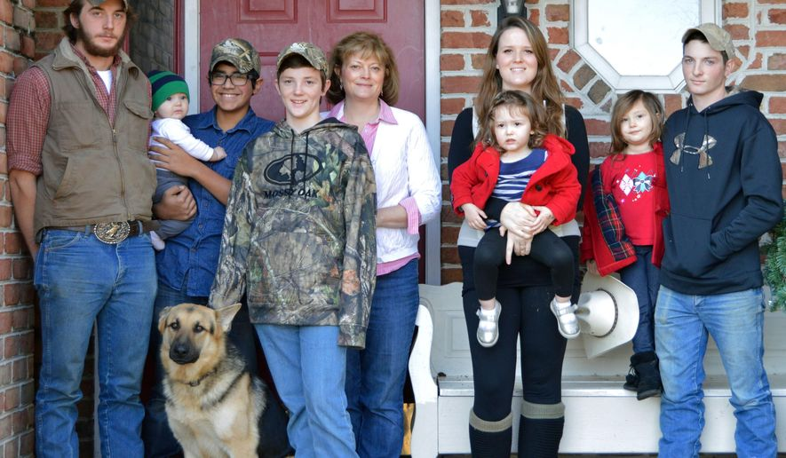ADVANCE FOR USE SUNDAY, DEC. 20, 2015, AND THEREAFTER - In this photo taken Dec. 5, 2015, Lou Ann Rieley, center, poses outside her home with her children and grandchildren, as well as Junior Rodriquez, left, who is currently living with the family, in Millsboro, Del. As a mother of 11 biological children, Rieley is used to a full house, but for the last 36 years, she has opened her home to those in need of a place to stay, mostly to children who have been abused or abandoned. (Hannah Carroll/The Daily Times via AP)  NO SALES; MANDATORY CREDIT  MBO