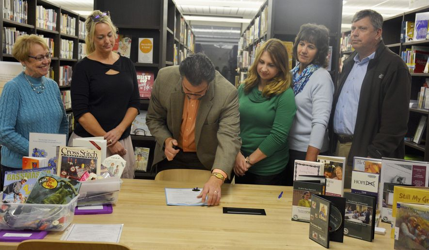 In this Nov. 12, 2015 photo, advocates for Alzheimer's caregivers and patients watch Mayor Jeff Bloemker sign a proclamation acknowledging the establishment of the Forget-Me-Not Center at the Effingham Public Library in Effingham, Ill. From left are Lenora Drees, Kelly Willenborg, Bloemker, Amy Sobrino, Shannon Nosbisch and Linus Nosbisch. (Bill Grimes/Effingham Daily News via AP) MANDATORY CREDIT