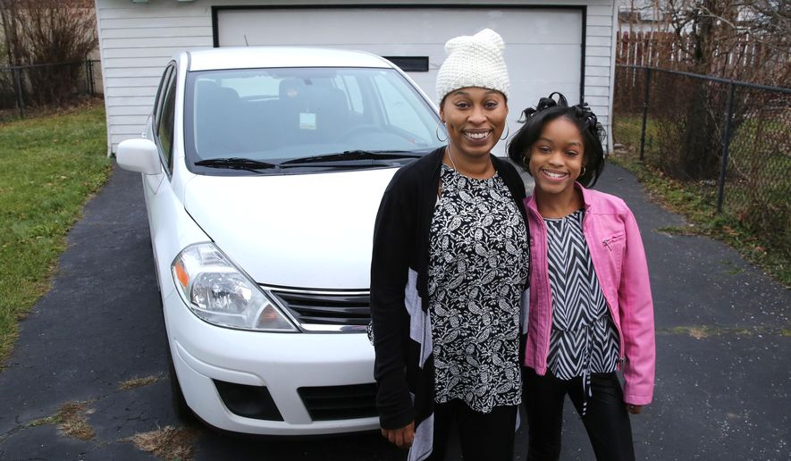 In this Friday, Dec. 11, 2015, photo, Diana Parks and her daughter Ania pose with the 2011 Nissan Versa that a repo man made the next payments on rather than seize the car, in Garfield Heights, Ohio. (Thomas Ondrey/The Plain Dealer via AP) MANDATORY CREDIT; NO SALES