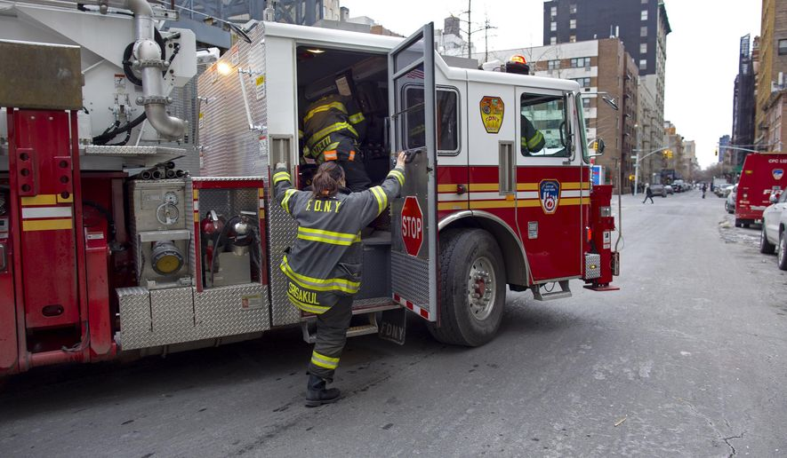 In this Jan. 28, 2014, file photo, a New York City firefighter jumps on a firetruck that just exited a Manhattan firehouse on the way to an emergency call in New York. About 4,400 current and retired firefighters with hearing loss have filed suits against a company that makes sirens, saying too-loud sounds have cost them their hearing, and the manufacturer should have included equipment that could have directed the sound. (AP Photo/Craig Ruttle, File)