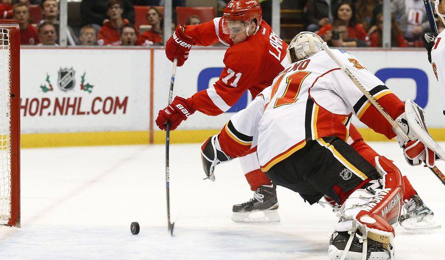 Detroit Red Wings center Dylan Larkin (71) scores on Calgary Flames goalie Karri Ramo (31) in the second period of an NHL hockey game Sunday, Dec. 20, 2015 in Detroit. (AP Photo/Paul Sancya)