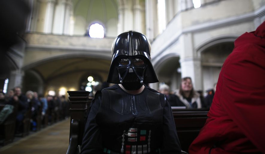A boy dressed as the Star Wars character Darth Vader attends a Star Wars themed church service, at the  Zion Church  in Berlin, Sunday, Dec. 20, 2015. About 500 people, some carrying light saber props or wearing Darth Vader masks, attended the service, more than twice as many as usual on a Sunday.  (AP Photo/Markus Schreiber)