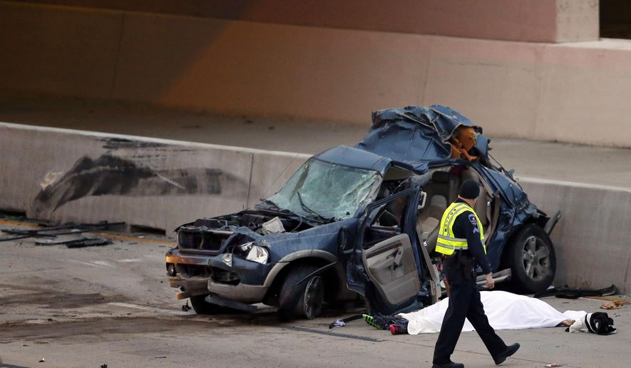 An Arlington police officer inspects an SUV which was hit by a Greyhound bus in the fast lane on westbound Interstate 30 near Collins St. in Arlington, Texas, killing one, under sheet, in the vehicle early Sunday, Dec. 20, 2015. The woman died after the vehicle she was traveling in stalled on the north Texas interstate after crashing into a barrier and was hit by the Greyhound bus. (Tom Fox/The Dallas Morning News via AP) MANDATORY CREDIT; MAGS OUT; TV OUT; INTERNET USE BY AP MEMBERS ONLY; NO SALES)