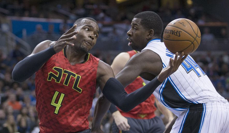 Atlanta Hawks forward Paul Millsap (4) tries to grab the ball against Orlando Magic forward Andrew Nicholson (44) during the first half of an NBA basketball game in Orlando, Fla., Sunday, Dec. 20, 2015. (AP Photo/Willie J. Allen Jr.)